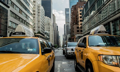 Yellow taxis drive down a road lined with tall buildings in New York city.
