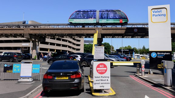 A sign for valet parking at the entrance of the Valet Car Park at Birmingham Airport which sits under the Air-Rail link running from the train station to the airport.