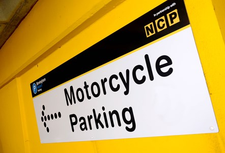 ImgAlt: A sign reading 'motorcycle parking' on a yellow wall at Birmingham Airport in Car Park 2.