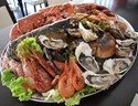 A large selection of fresh seafood on a platter, including oysters, prawns and lobster